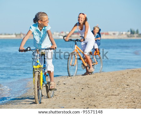Cute girl with her mother and brother ride bikes along the beach. Focus on mother