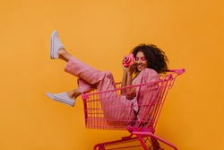 Cute girl with pink camera posing on yellow background. Studio portait of smiling african young woman in shopping cart.
