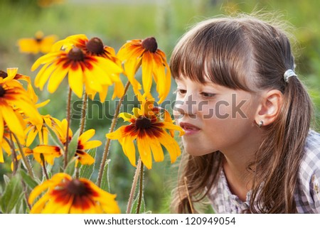 Cute girl with pleasure smell the wildflowers