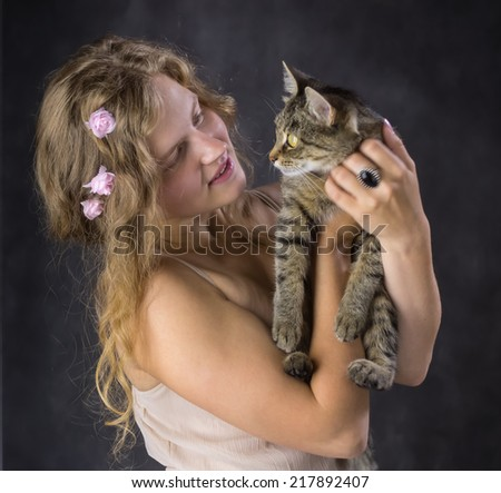 cute girl with roses in her hair and with a cat on his hands