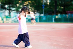 Cute girl with sweet smile looked down at stadium floor. Asian children are exercising. Child enjoy outdoor exercise. Kid play sports with family in public areas. Baby wearing pink shirt is 3-4 years.