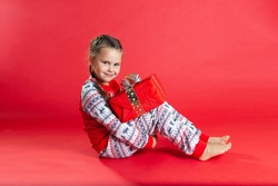 cute girl with two pigtails and in Christmas pajamas sitting on the floor, hugging her knees, holding a gift box, isolated on a vibrance background.