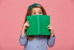 Cute girl 5-6 years wearing hair hoop having fun while reading interesting book with eyes wide open, isolated over pink background