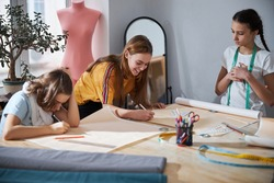 Cute girls drafting sewing patterns in dressmaking studio
