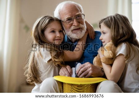 Cute girls hugging their grandpa after watching his magic tricks with bunny in a hat Stockfoto ©