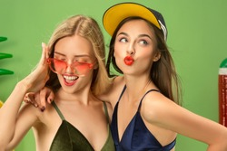 Cute girls in swimsuit posing at studio. Summer portrait caucasian teenagers on a green background. Concept of summer, summertime, recreation, break, vacation, travel.