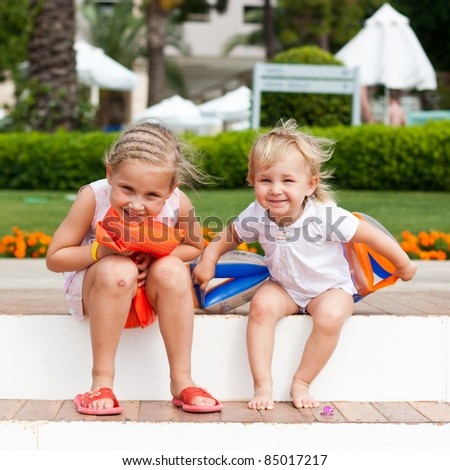 Cute girls preparing to go to swim in armbands in the resort