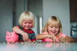 cute girls saving money, kids put coins into piggy bank