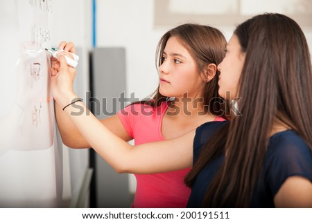 Cute girls working together to solve a math problem in front of a white board at school