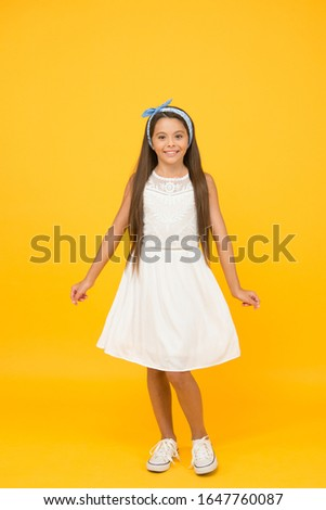 Cute girly girl. Happy girl yellow background. Fashion look of small girl. Little girl wear long brunette hair. Beauty salon. Fashion and style. Shop kids clothing and baby clothes. Girls day.