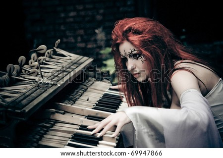 cute gothic girl plays on piano