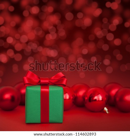 Cute green gift with red christmas balls on red abstract light background