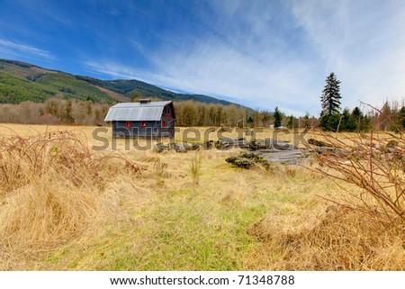 Cute grey and red rustic old barn in the field. Build in 1907 old shed in Ashford, near Mt.Rainier, Washington State