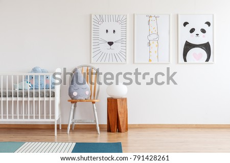Cute grey raindrop shaped cushion placed on wooden chair standing next to white crib in bright baby room interior #791428261