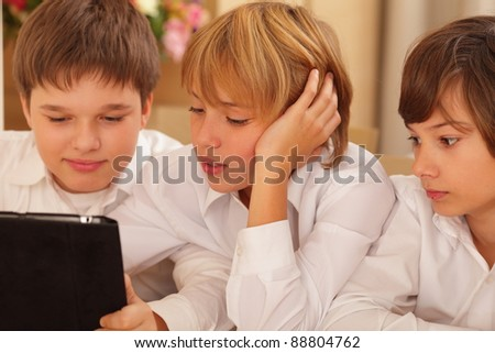 Cute group of boys playing on portable computer at school