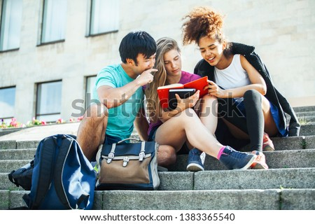 cute group of teenages at the building of university with books huggings, diversity nations students lifestyle #1383365540