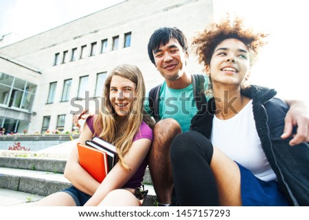 cute group of teenages at the building of university with books huggings, diversity nations students lifestyle