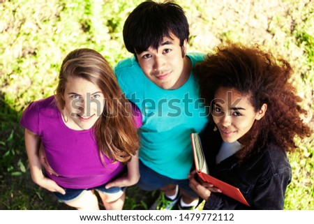 cute group of teenages in green park at summer with books huggings, diversity nations real students lifestyle