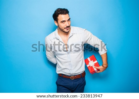 cute guy hiding a christmas gift behind him on blue background