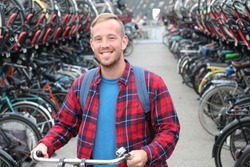 Cute guy in modern bicycle parking lot