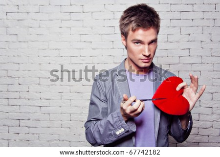 Cute guy in the studio with red heart in his hands and knife