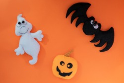 cute halloween concept. hand made kids toy. pumpkin head, ghost, bat on orange background. top view