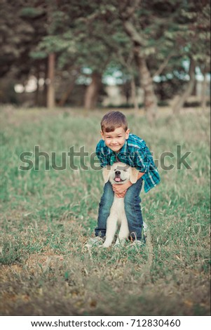 Cute handsome boy teen with blue eyes playing outdoor amazing white pink labrador retriever puppy enjoying summer sunny day vacation weekend with full happyness.Happy smiling kid with best friend #712830460