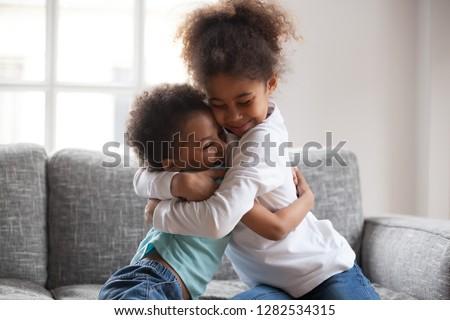 Cute happy african american siblings hugging cuddling feeling love and connection, smiling mixed race kid girl sister embracing little boy brother sitting on couch, 2 children good relationships
