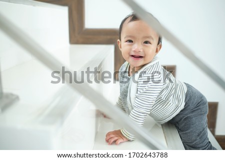 Photo of  Cute happy Asian 10 months old toddler baby girl child climbing up stairs at home alone, Looking and smiling at camera, Movement, Balance & Coordination, Stair climbing developmental milestone concept
