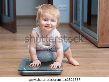 Cute happy baby check own weight on home scales