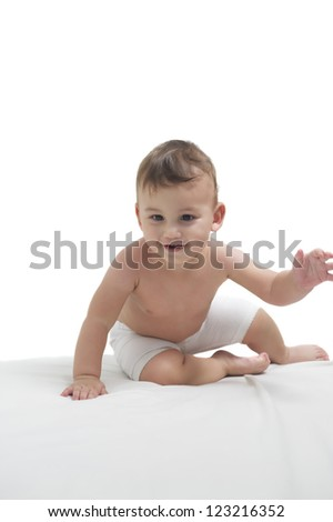 Cute happy baby gambling on a white towel