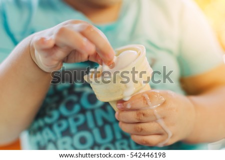 Cute happy baby girl are eating ice cream in summer. Picture for concept of sweet ,fat ,obesity and diabetes in children.Soft focus.