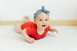 cute happy baby girl in red jumpsuit on white background