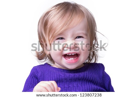 Cute happy baby is laughing fearless and freely with her new teeth, looking in to camera. Isolated on white.
