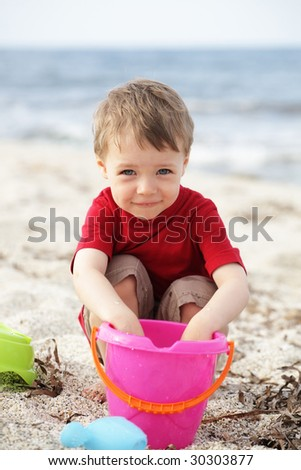 cute happy boy playing on the beach - stock photo