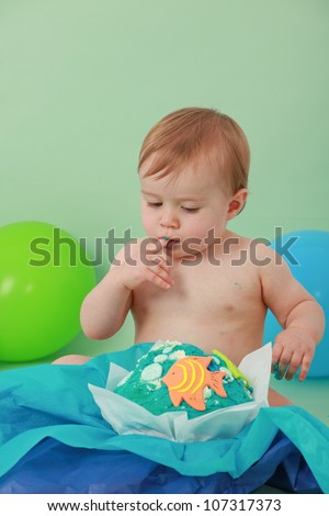 Cute happy brunette baby boy with closed eyes is tasting his blue butter icing on his ocean themed giant fish birthday cupcake licking sticky icing off his fingers and sitting on green background