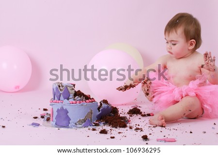 Cute happy brunette baby girl in pink tutu and topless sitting on pink background by her birthday double tier pink and purple butter iced cake with dirty sticky hands looking at her destroyed cake
