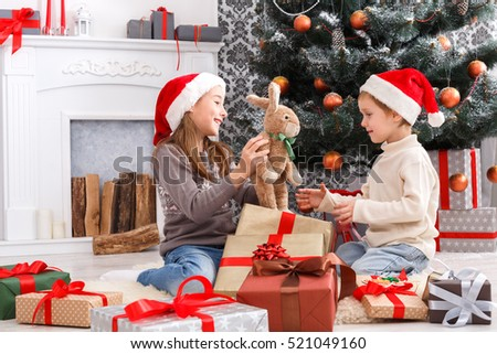 Shutterstock Cute happy excited children, boy and girl in santa hats unwrap rabbit christmas present on holiday morning in beautiful room. Sister and brother open Xmas gifts near decorated tree and fireplace.