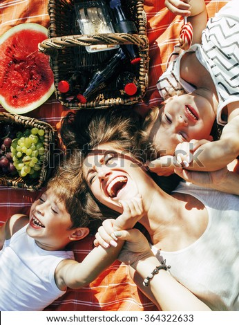 cute happy family on picnic laying on green grass mother and kids, warm summer vacations close up, brother and sister