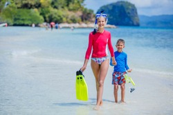 Cute happy girl and boy with scubadiving equipment walking on tropical beach