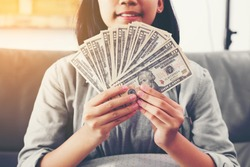 cute happy girl holding in hand a lot american dollarsspending money or profit from business operations concept