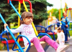 cute happy girl, kid having fun on swings at playground