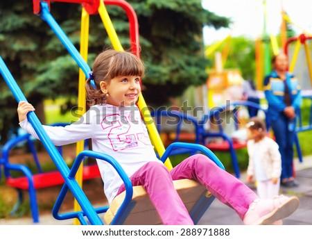 cute happy girl, kid having fun on swings at playground