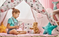 Cute happy girl plays at home. Funny lovely child is having fun in children room. Girl plays tea-party and drinks tea from cup.