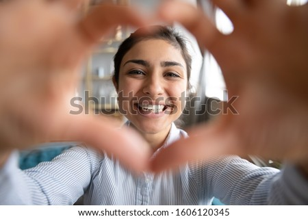 Cute happy indian girl making heart shape hand gesture looking at camera, funny smiling ethnic young single woman blogger laughing face showing love sign symbol, dating concept, close up portrait