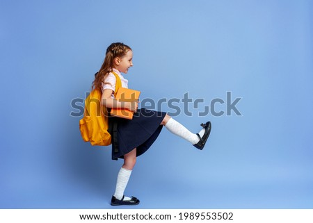 Cute happy kid in uniform. raises his leg high and runs on purple background. child with backpack. little girl is ready for school. Dynamic images that go back to conceptual school. holidays begin. Stockfoto ©