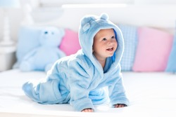 Cute happy laughing baby boy in soft bathrobe after bath playing on white bed with blue and pink pillows in sunny kids room. Child in clean and dry towel. Wash, infant hygiene, health and skin care