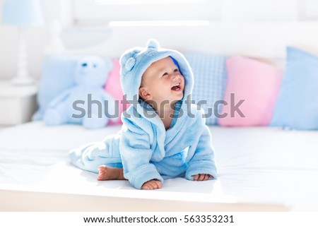Cute happy laughing baby boy in soft bathrobe after bath playing on white bed with blue and pink pillows in sunny kids room. Child in clean and dry towel. Wash, infant hygiene, health and skin care #563353231