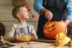 Cute happy little boy helping his father to carve Halloween pumpkin while standing in kitchen at home and preparing for autumn holiday, family of two son and dad making Jack-o-Lantern together