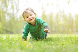 Cute happy little Boy (7 months old) discovering nature. Crawling in the Grass on a Sunny Summer Day while Smiling